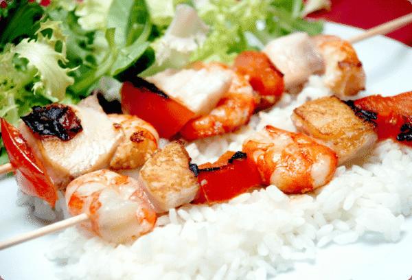 Brochetas de pescado con arroz de guarnición y ensalada