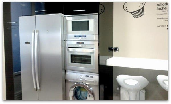 Lavadora, horno y microondas en un torre y al lado la nevera